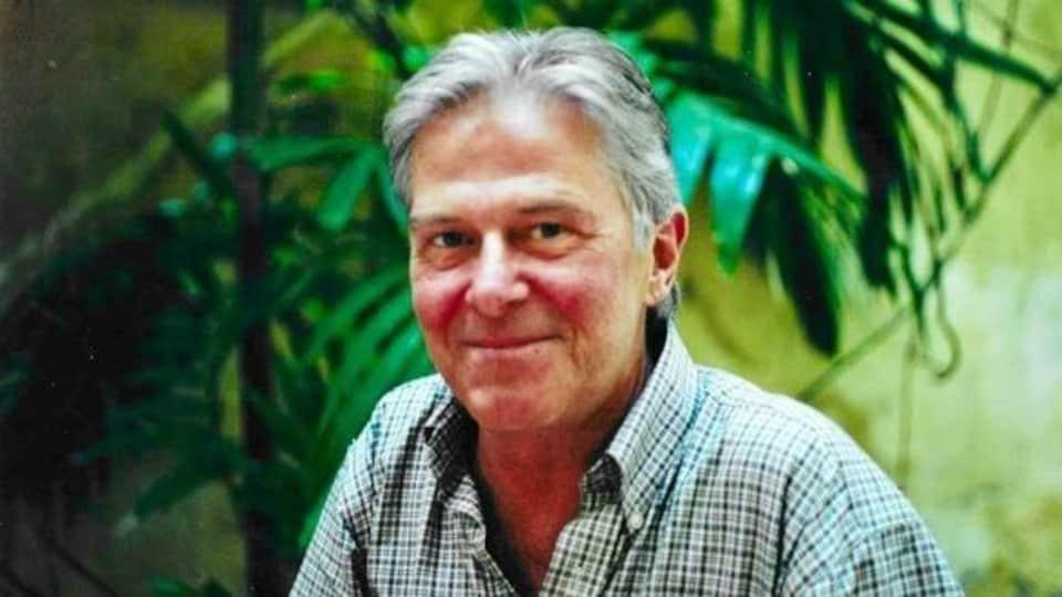Le comédien Hubert Gagnon, dehors, qui sourit pour la photo.