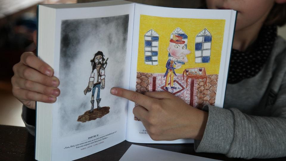 Un petit garçon pointe un dessin du doigt.