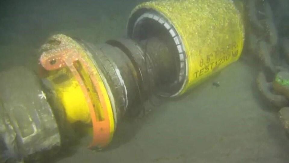Gros plan sur un raccord qui relie deux conduites sous-marines.
