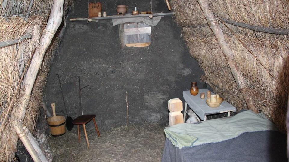 L'intérieur de la hutte avec un lit, une table et des objets.