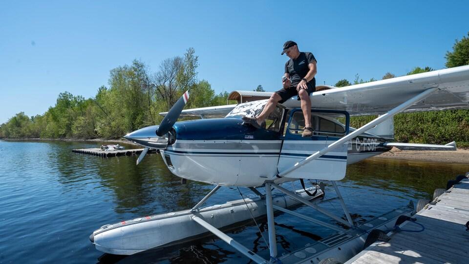 Un homme est posé sur un hydravion qui flotte sur l'eau.
