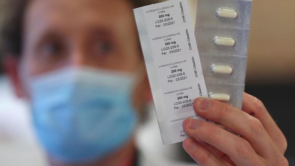 Un pharmacien exhibe les comprimés dans leur emballage.