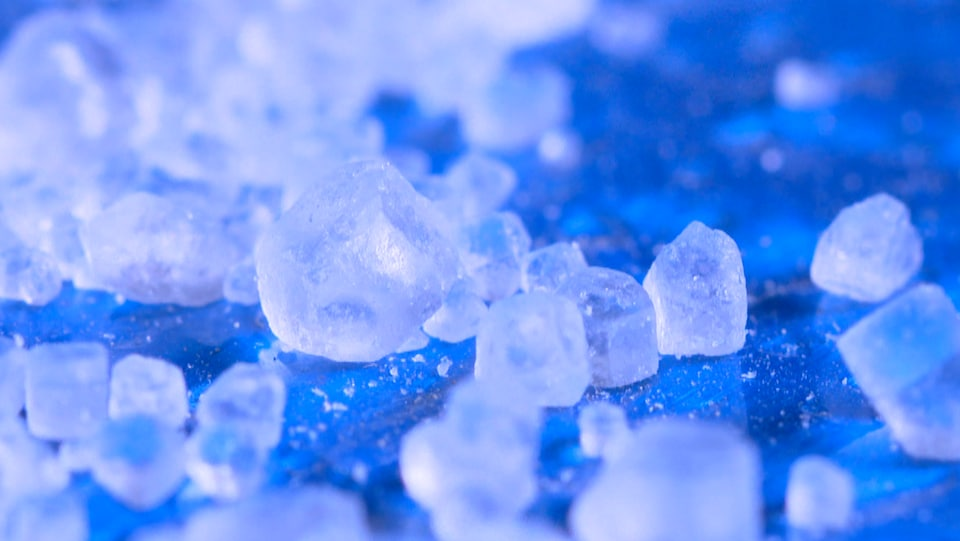 On voit en gros plan les cristaux transparents, sur fond bleu.