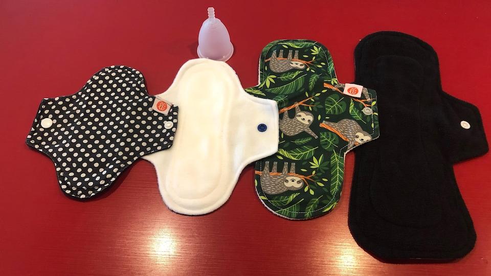 Quatre serviettes hygiéniques lavables et une coupe menstruelle.
