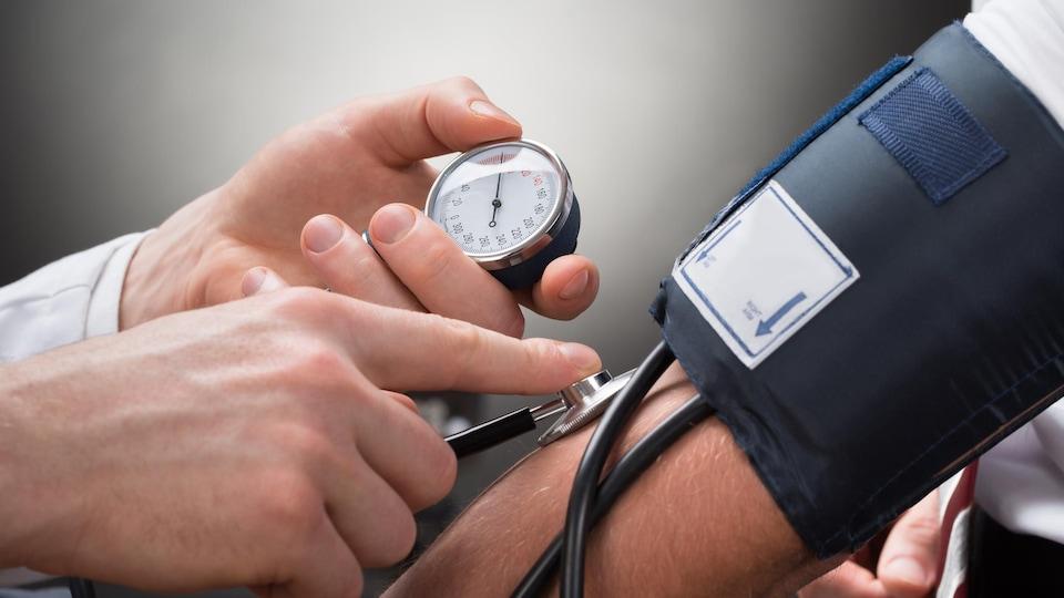 Un médecin prend la pression d'un patient.