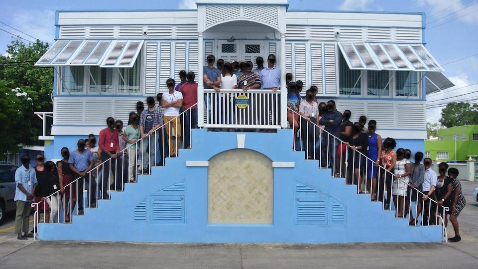 Il s'agit d'une trentaine de personnes devant des bureaux à la Barbade.