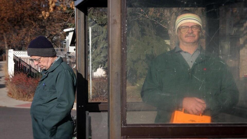 Deux hommes en tenue de travail attendant l'autobus.