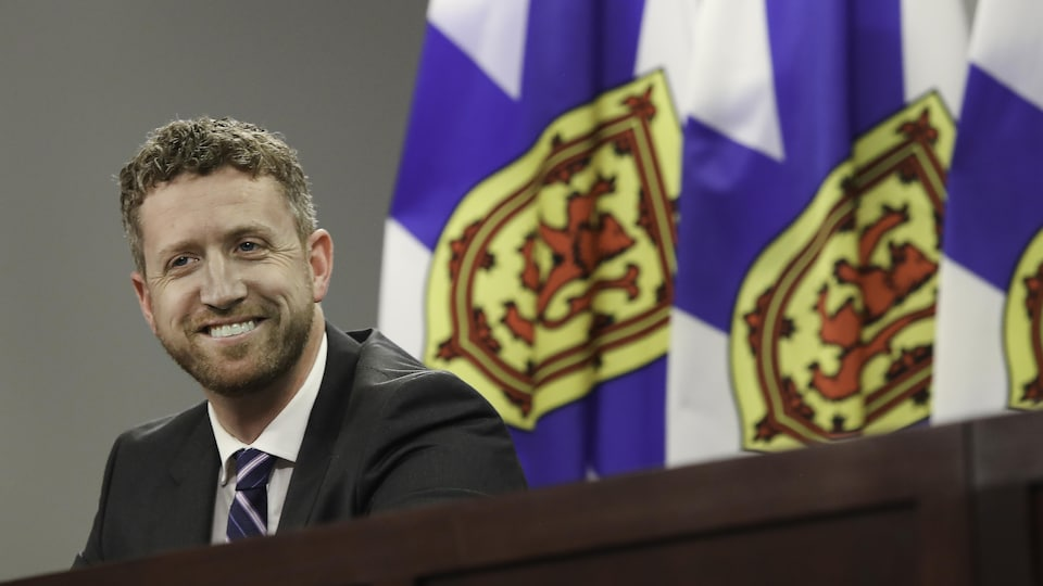 Iain Rankin souriant devant des drapeaux de la Nouvelle-Écosse.