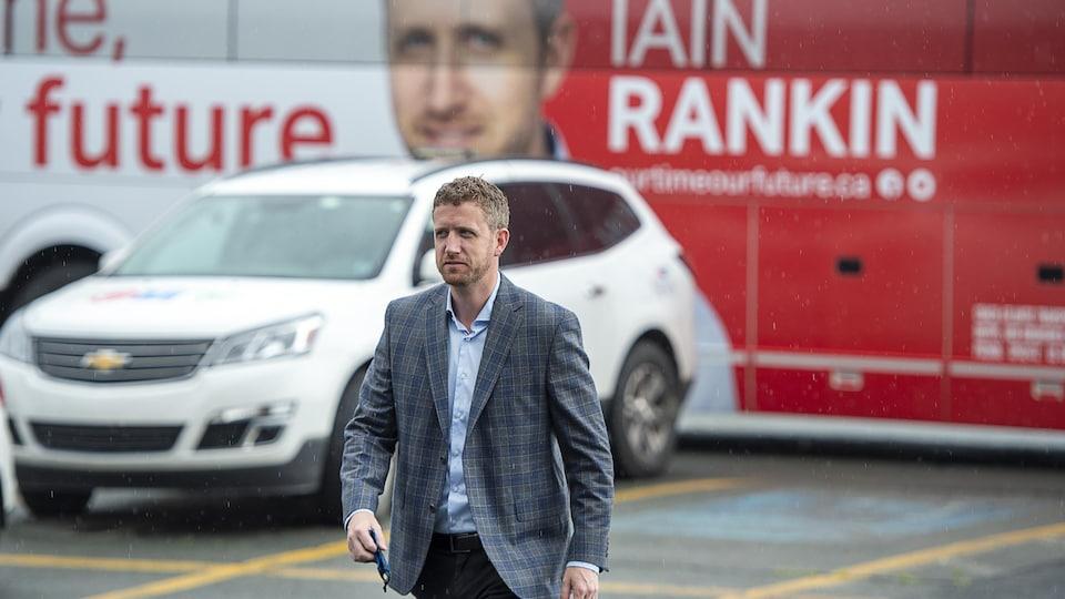 Iain Rankin marche en sortant de son autobus de campagne électorale.