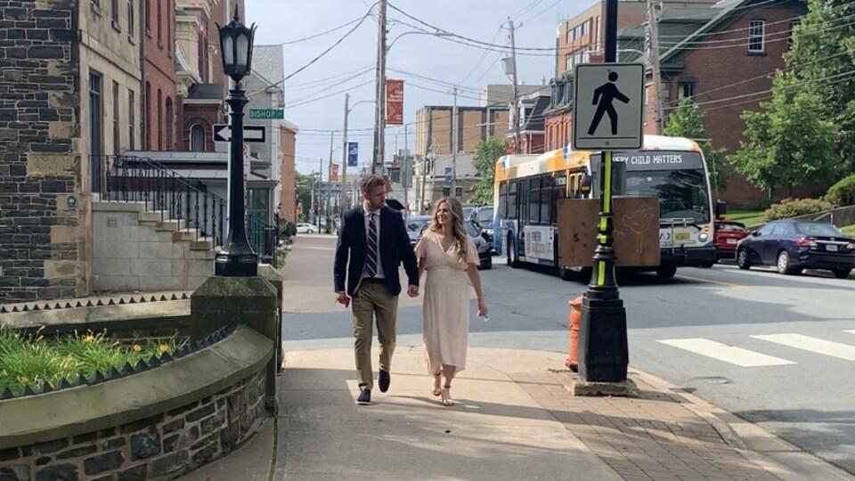 Le couple marche main dans la main en bordure d'une rue où circulent des voitures et un autobus.