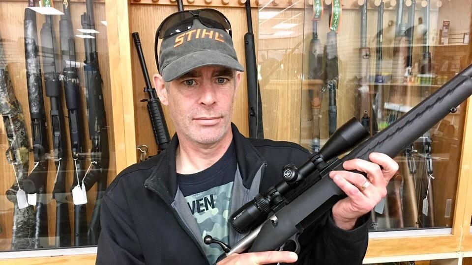 Ian Kendrick, propriétaire d'un magasin de chasse et pêche de Grenville-sur-la-Rouge, qui tient un fusil de chasse.
