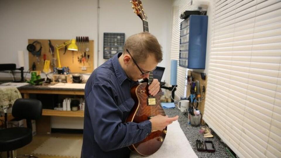 Un luthier répare une guitare.