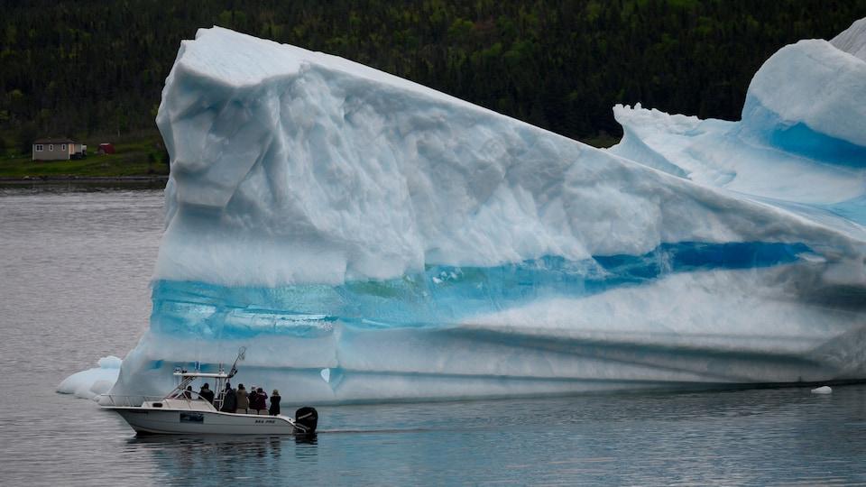 Quelques touristes à bord d'un bateau qui passe devant un iceberg.