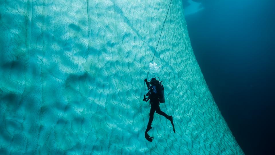 Une plongeuse au plus près d'un iceberg bleuté.