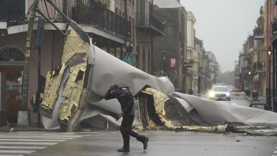Un homme passe à côté d'un toit étalé dans la rue.