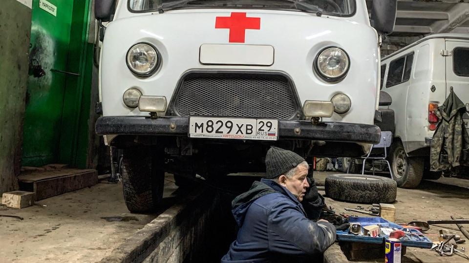 Il travaille sous le véhicule.