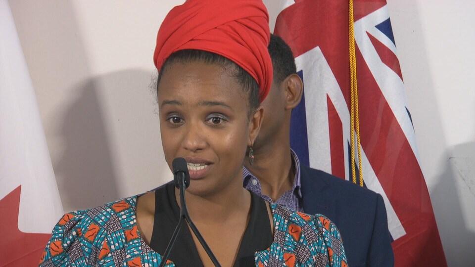Une femme avec les cheveux noués sous un foulard derrière un micro lors d'un point de presse.