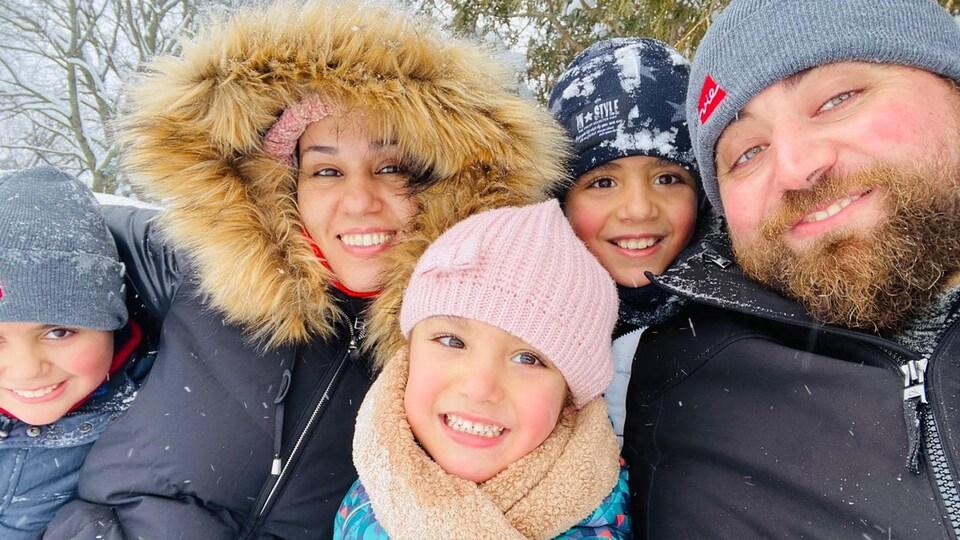 Ikram Khaouani, son mari et ses trois enfants sourient habillés de vêtements d'hiver à l'extérieur.