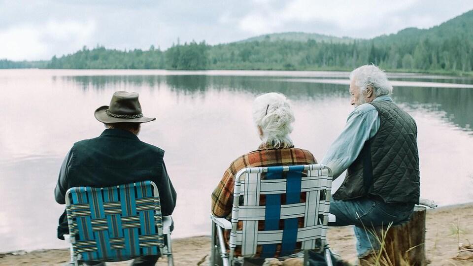Trois personnes âgées font face à un lac.