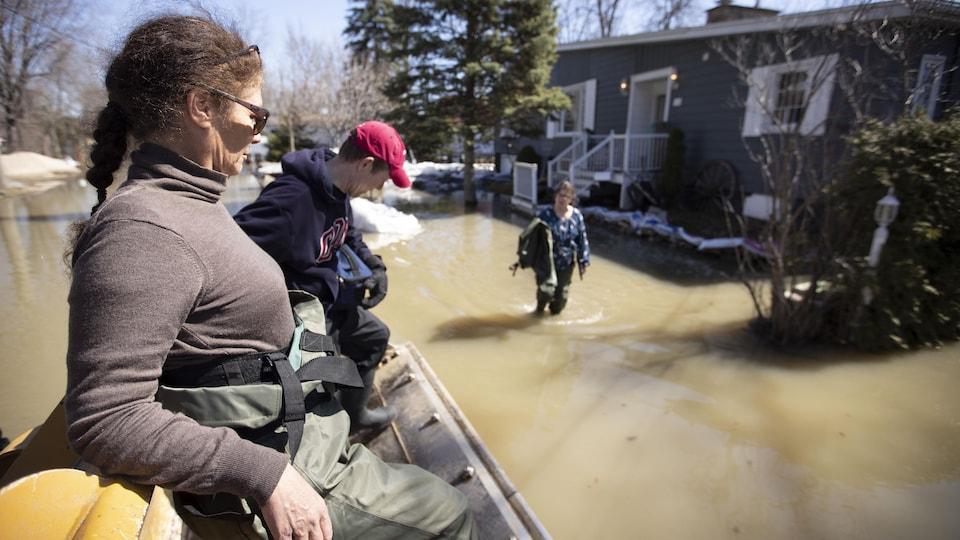 Une femme et un homme sont transportés dans une pelle de tracteur. Une femme devant une maison située tout près a les pieds dans l'eau.