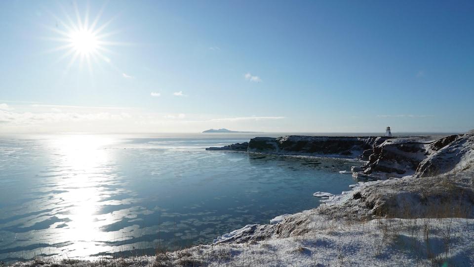 Le phare du Cap-Alright aux Îles-de-la-Madeleine au loin avec un soleil très puissant frappant la mer au mois de février. On voit aussi au loin d'île d'Entrée.