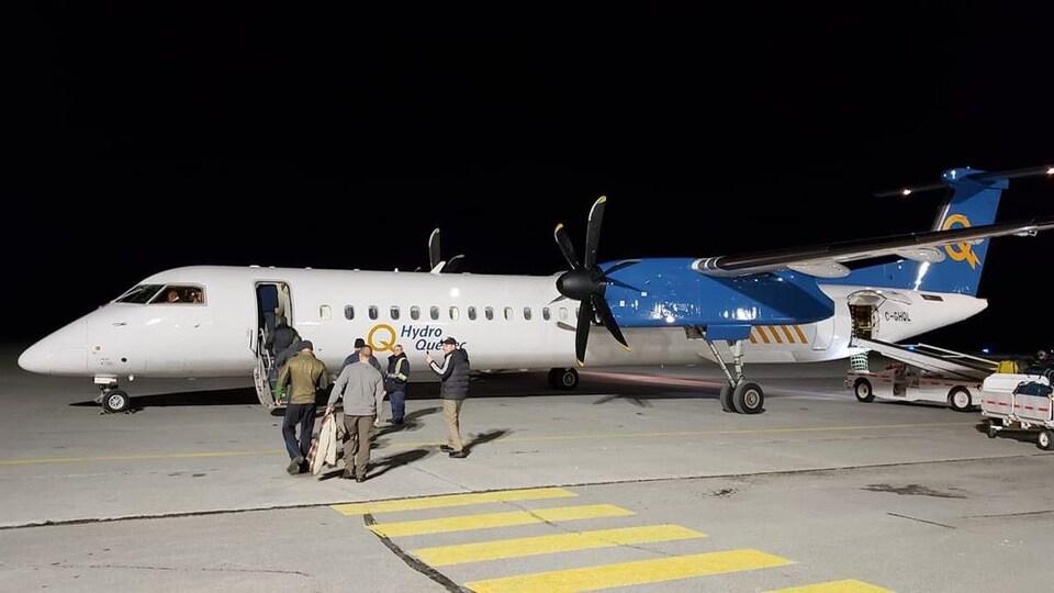 Des passagers montent à bord d'un avion identifié d'Hydro-Québec