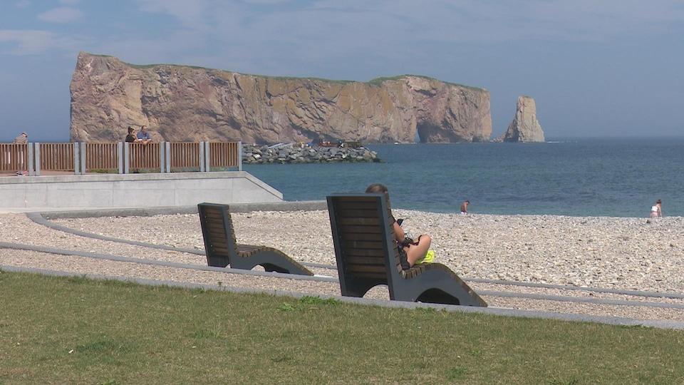 Une femme est assise sur une chaise longue sur une plage devant le rocher Percé.