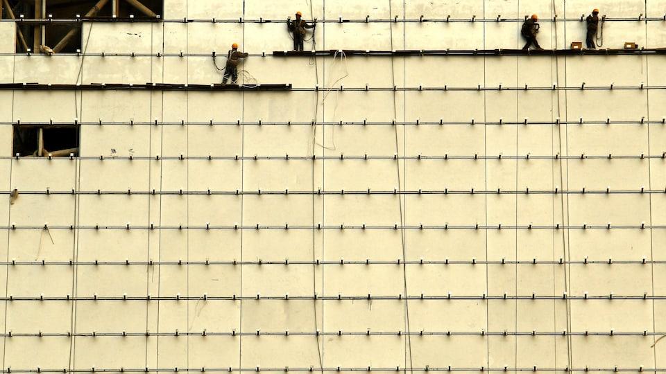 Des travailleurs sont debout sur des planches de bois à l'avant d'un bâtiment en construction dans le centre de Pékin, le 13 février 2012.