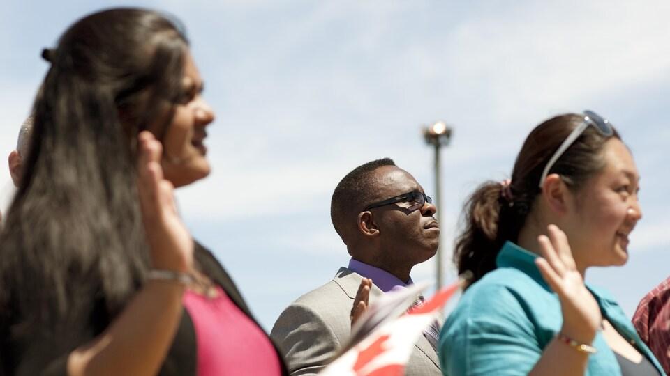 Des immigrants lors d'une cérémonie d'assermentation pour l'obtention de la citoyenneté canadienne