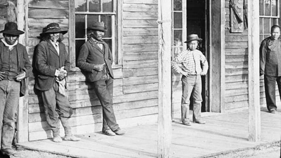 Des hommes se tiennent devant un magasin.