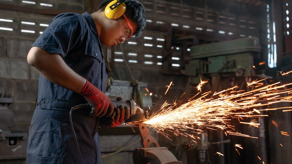 Un homme utilise de la machinerie dans une usine.