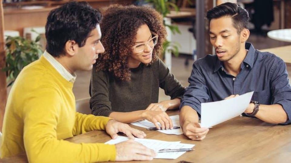 Trois personnes autour d'une table examinent des documents.