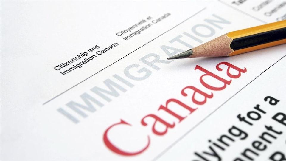Un formulaire d'Immigration Canada avec un crayon à mine déposé par-dessus.