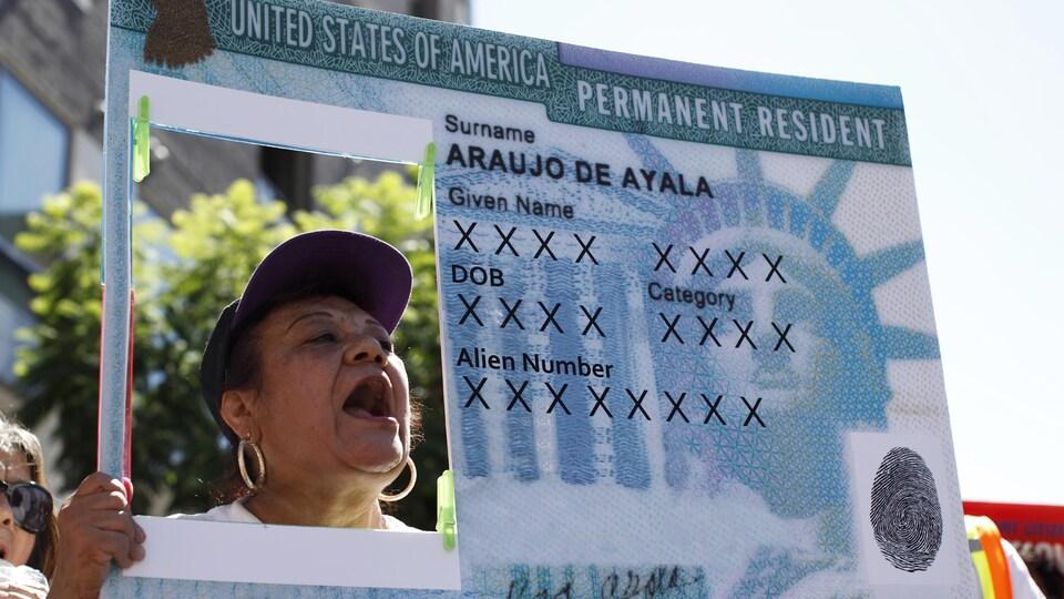 Une femme dans une manifestation tient une pancarte qui représente une carte verte américaine.