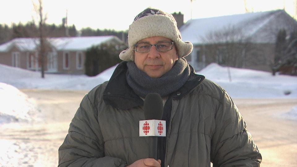 Un homme tenant un micro de Radio-Canada pose devant la rue en hiver
