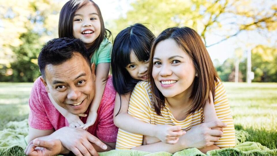 Une famille pose pour la caméra dans un parc.