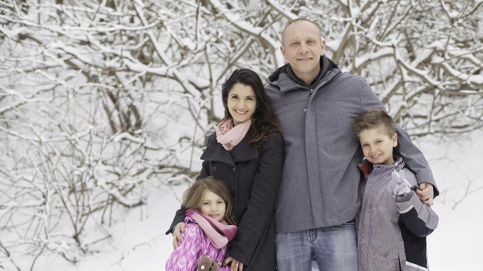 Un couple avec deux enfants, sous la neige
