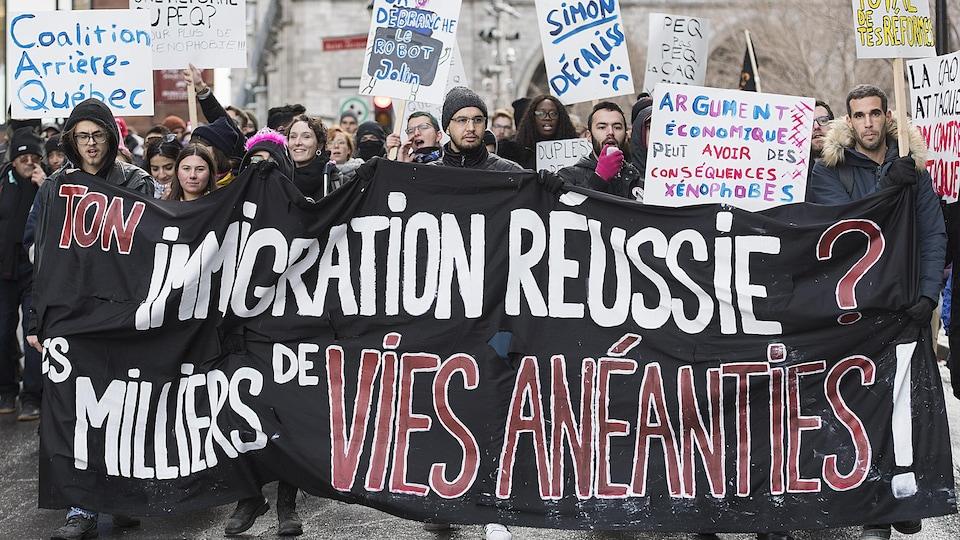 Des manifestants dénoncent les politiques d'immigration du gouvernement du Québec.