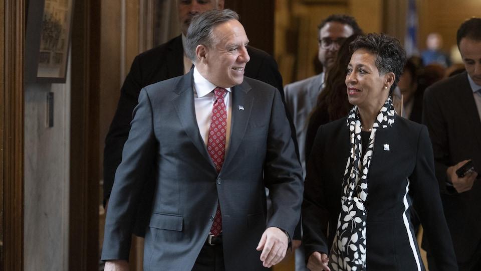 François Legault discute avec Nadine Girault en marchant dans un couloir de l'Assemblée nationale.