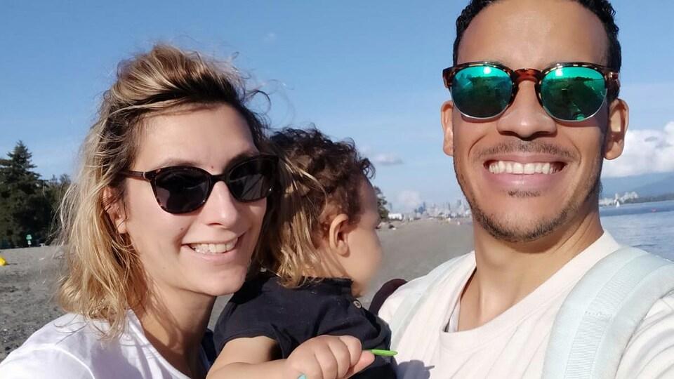 Une femme et un homme avec un bébé avec la plage derrière eux.