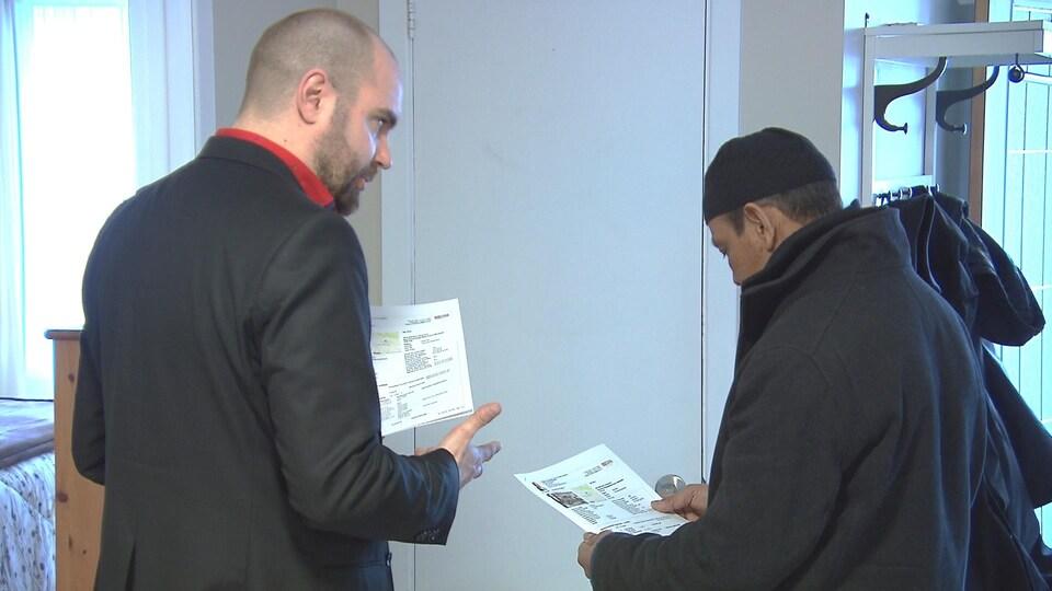 L'agent immobilier et le visiteur regardent sur une feuille de papier les spécifications de la maison à vendre.