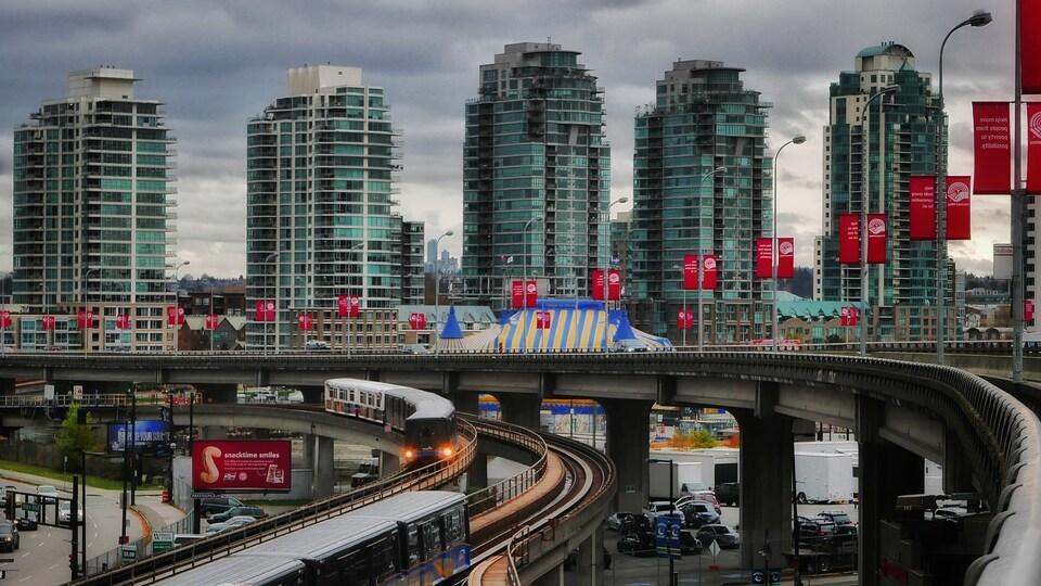 Cinq tours d'habitation et les rails du SkyTrain passant au-dessus d'un parc de stationnement à Vancouver.
