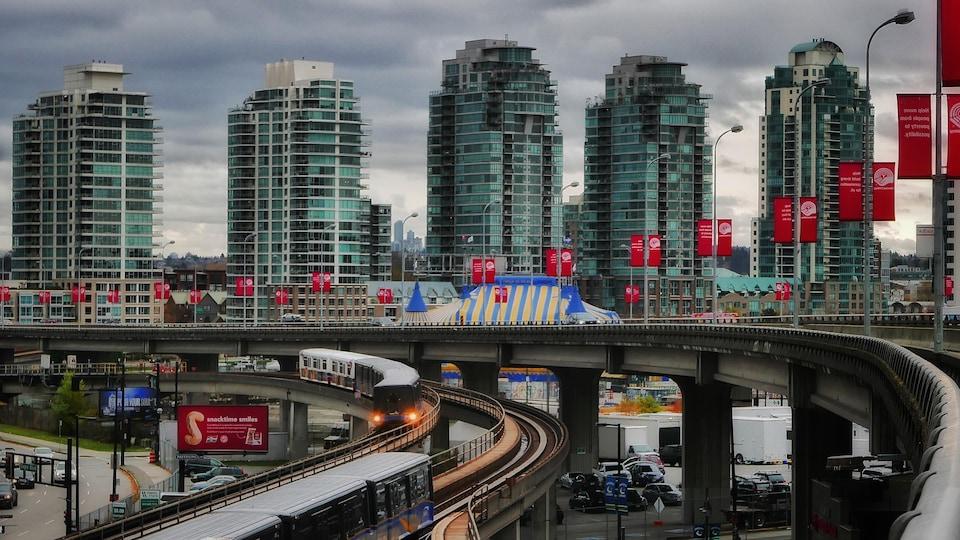 Cinq tours d'habitation et les rails du SkyTrain  passant au-dessus d'un parc de stationnement à Vancouver