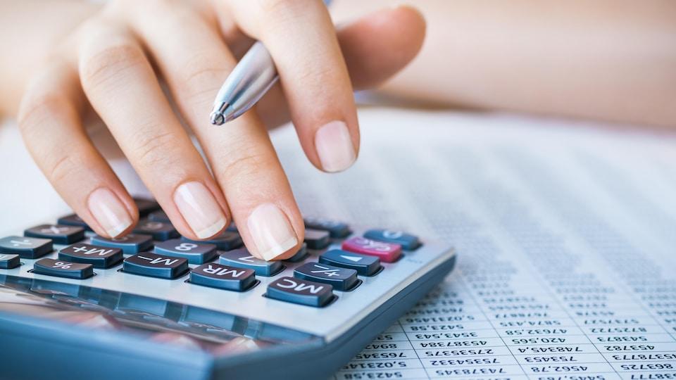 Une personne tenant un stylo dans sa main semble taper des numéros. sur calculatrice.