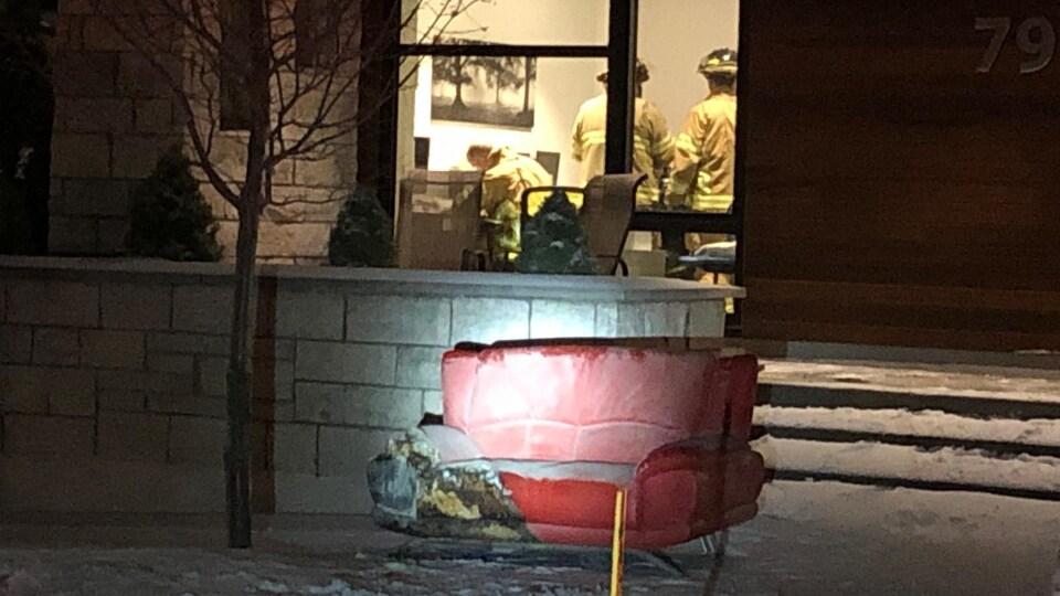 Des pompiers dans une résidence avec un canapé brûlé à l'extérieur.