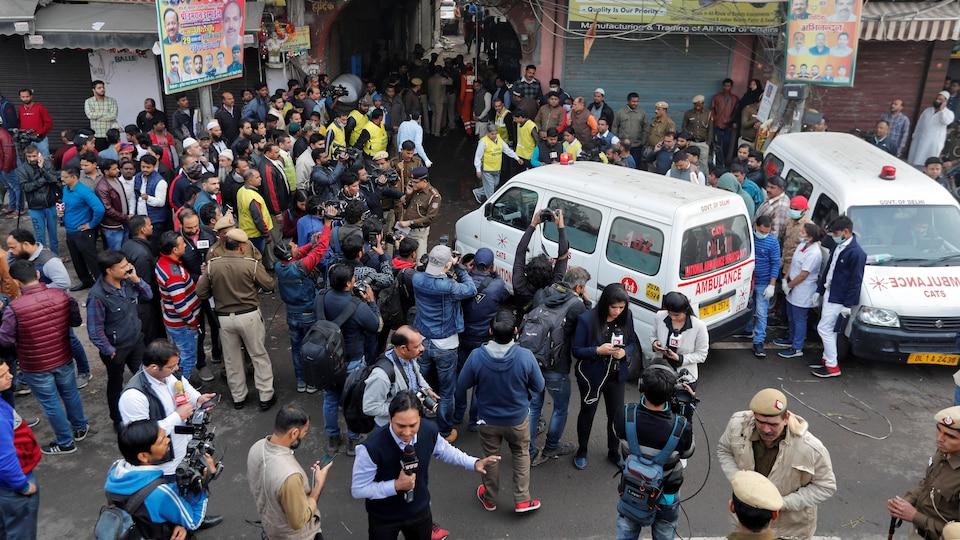 Une ambulance se dirige vers un petit tunnel, entourée de journalistes et de la foule.