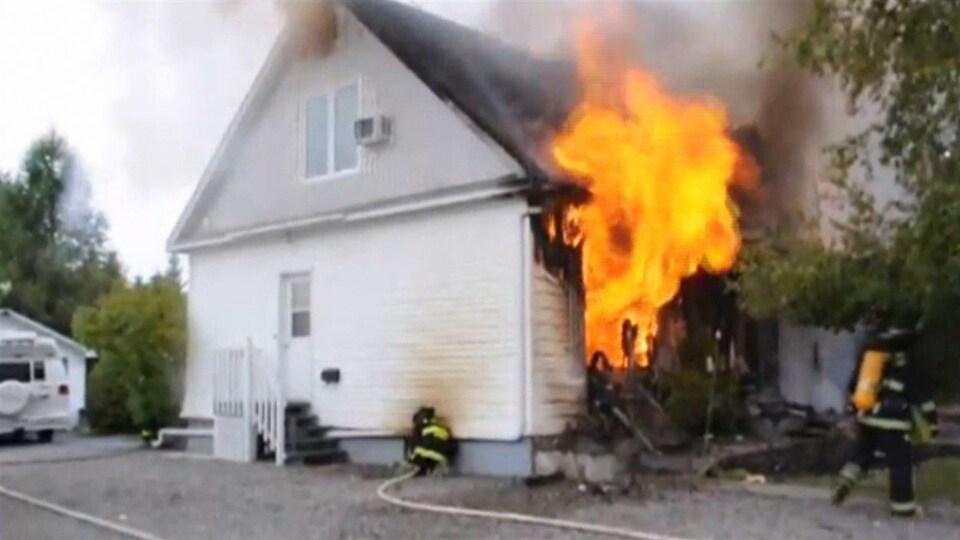 Une maison en vinyle blanc dont un des côté est en flammes.