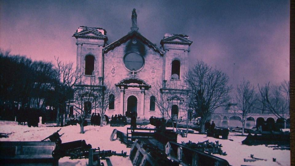 Photographie en noir et blanc de la basilique Sainte-Anne-de-Beaupré après l'incendie du 29 mars 1922.  On aperçoit la façade de pierre, qui est lourdement endommagée. Les deux clochers ont été détruits.