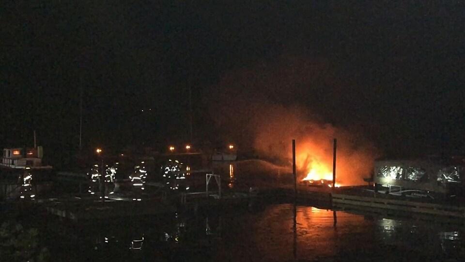 Des pompiers arrosent l'embarcation en flamme.