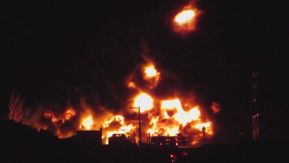 Des flammes s'élèvent dans le ciel.